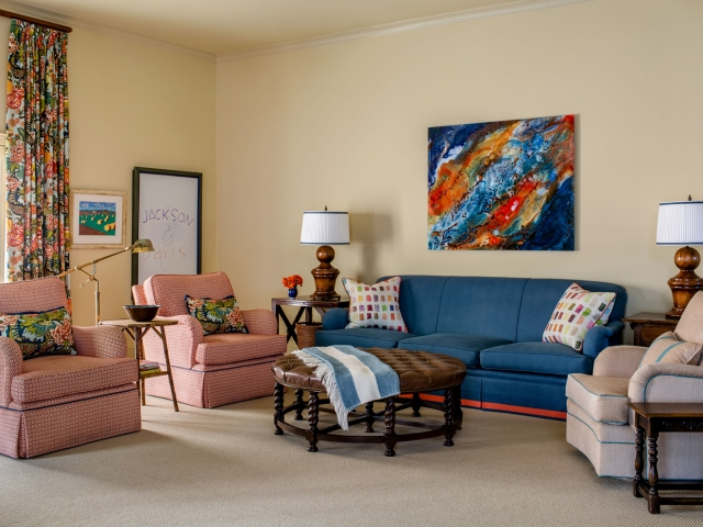Beretania Circle Residence 1 family room blue red bright floral print round leather tufted ottoman Pebbles Nix Interiors