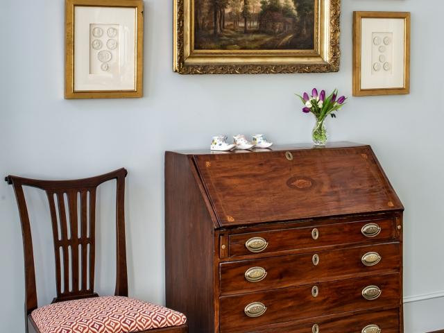 Beretania Circle Residence 3 master bedroom antique writing desk gold framed paintings grey wall and rug Pebbles Nix Interiors